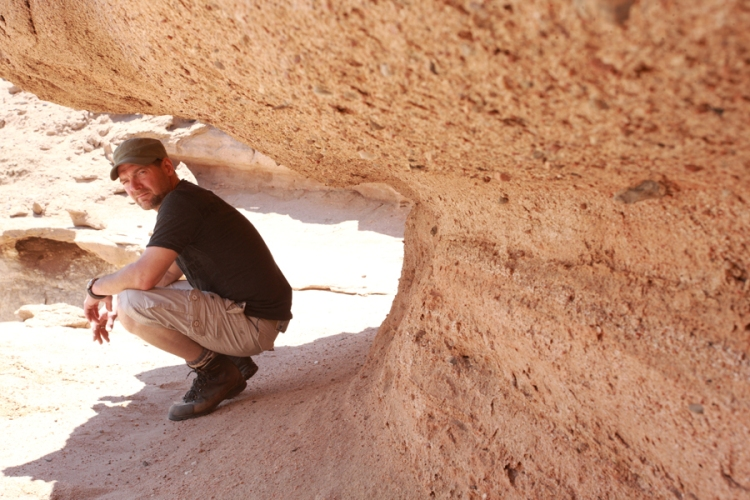 Survivorman – Les Stroud crouching down in a desert cave whilst looking at the camera.
