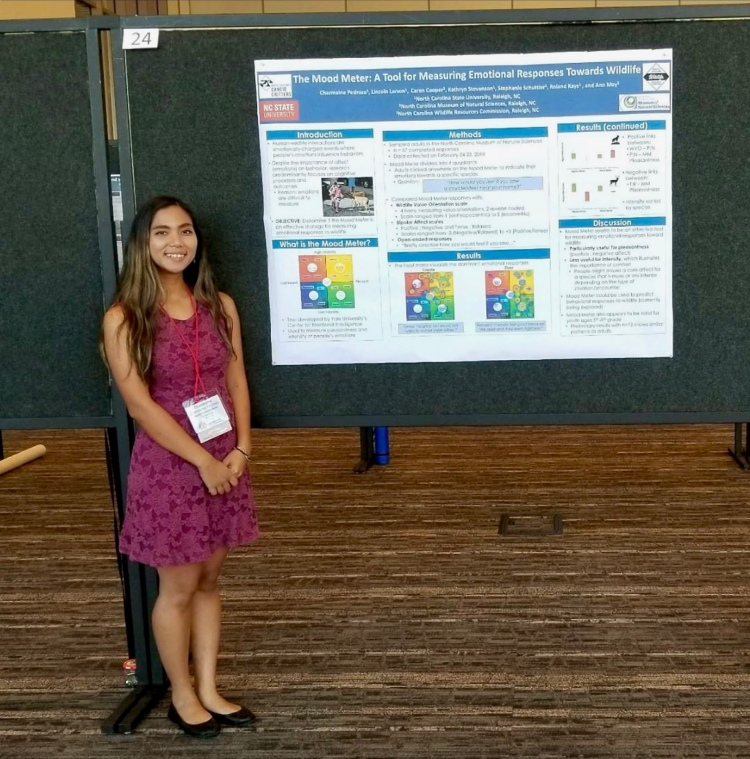 A young, professionally-dressed woman standing next to a research poster.