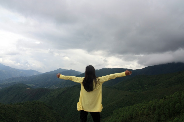 A young woman standing on a mountaintop and extending her arms like the letter t.