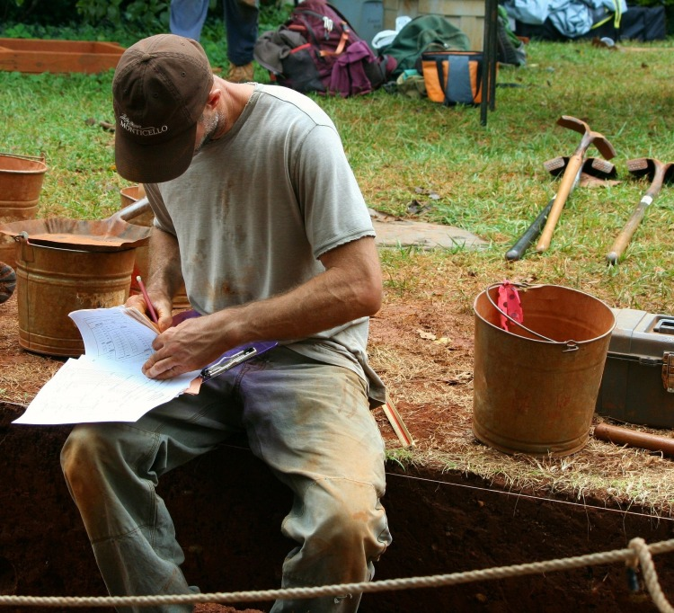 An archaeologist filling out paperwork at an excavation.