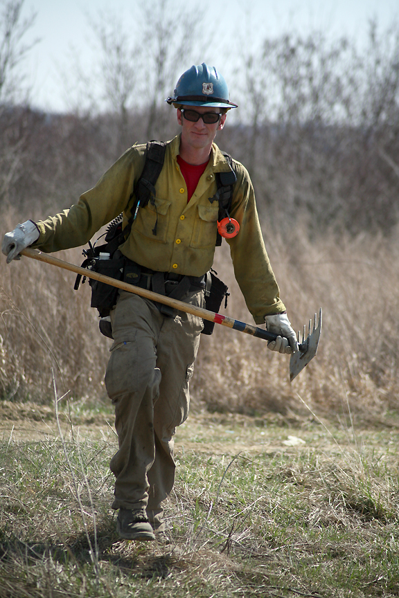 A firefighter carrying a McLeod